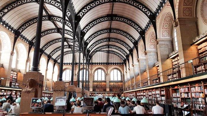 Photo 1 of Biblioteque Genevieve interior, a large room with very high vaulted ceilings and arched windows. The walls are lined with bookshelves and there are desks all filled with people in the centre.