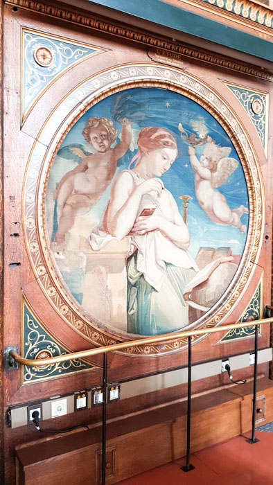 Photo 2 of Biblioteque Genevieve interior, showing a circular wall mural of a lady and two cherubs. The mural has a decorative wooden border around it.