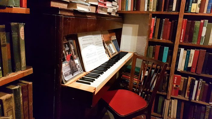 Photo of the interior of Shakespeare & Company, an upright piano surrounded by books, a wooden chair with a red seat sits at it.