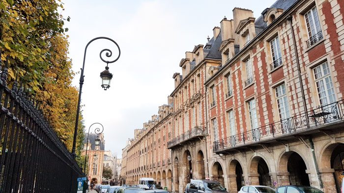 Photo of the street the Victor Hugo Museum is on. On the left are tall trees, a black metal fence and a fancy lamp post. On the right is a long row of red and white brick buildings with arches on the ground level and small decorative balconies in front of the upper windows.
