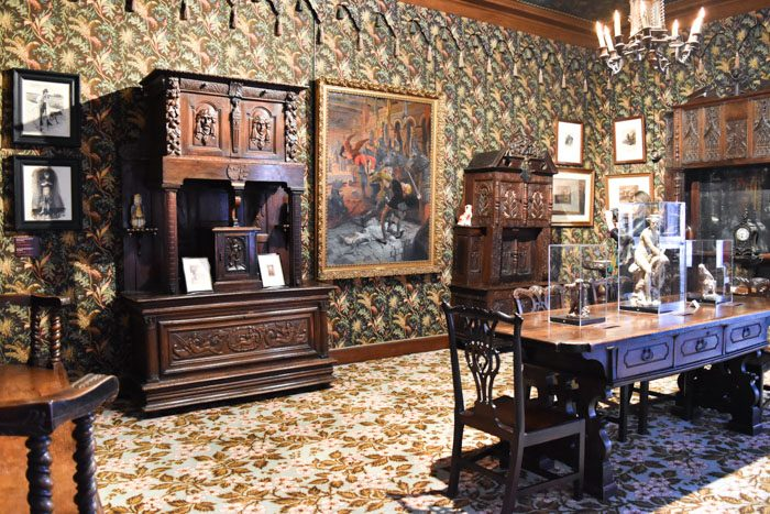 Photo of the interior of the Victor Hugo museum, showing a room with dark floral patterned wallpaper, heavy dark wood furniture, 7 paintings on the wall in frames and a large dining table which has glass display boxes on top of it.