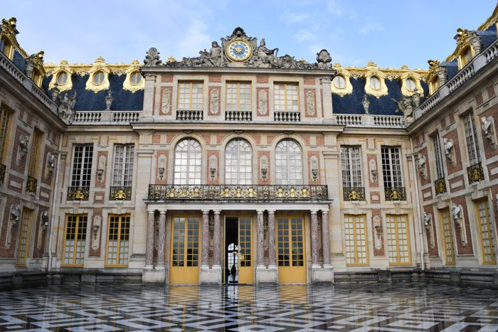 The front of the Palace of Versailles, a huge 3 storey building with a black and white patterned tile square, gilt decorations on the windows, balconies and windows. A huge clock dominates the center top, flanked by sculptures.