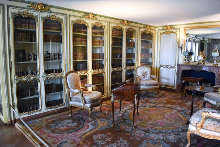 Photo of the interior of Versailles, a small room with a wall of bookcases on the left with green and gold decorative borders around the glass doors. On the right a mirror hangs above a fireplace. There is a beautiful pink and red rug on the floor and 4 padded armchairs with floral designs and a small wooden writing desk.