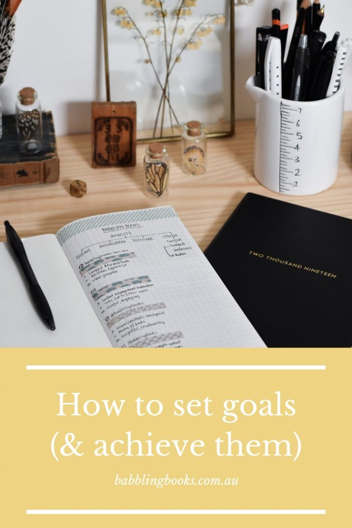 Graphic with image of journals and some vintage items on a desk. White text on a yellow background at the bottom says 'How to set goals (and achieve them)'