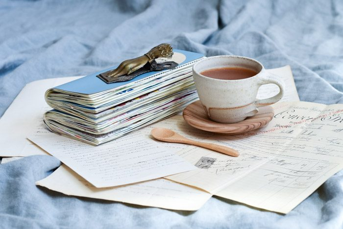 Creative journal ideas and inspiration, featuring a stack of journals, antique hand written letters and a cup of tea
