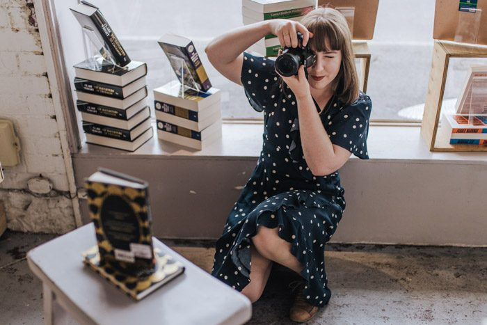 Tamsien West - Babbling Books, taking a photo in a bookstore, wearing a navy blue dress with white polka dots.
