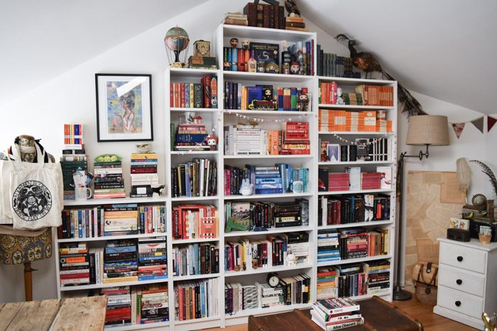 How to Organise Your Bookshelves - Room with white bookshelves of various sizes and heights filled with colourful books and trinkets.