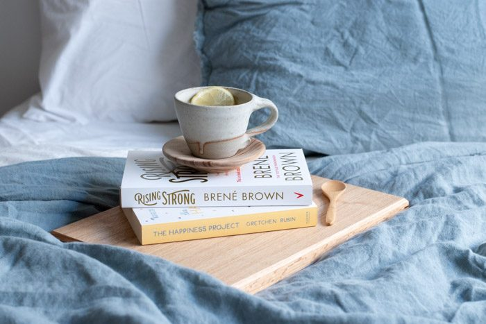 4 Ways to care for yourself as a creative. Images shows a closeup of a bed with blue and white linen. Two books are stacked with a tea cup on top. The book titles are The Happiness Project by Grechin Rubin and Rising Strong by Brene Brown.