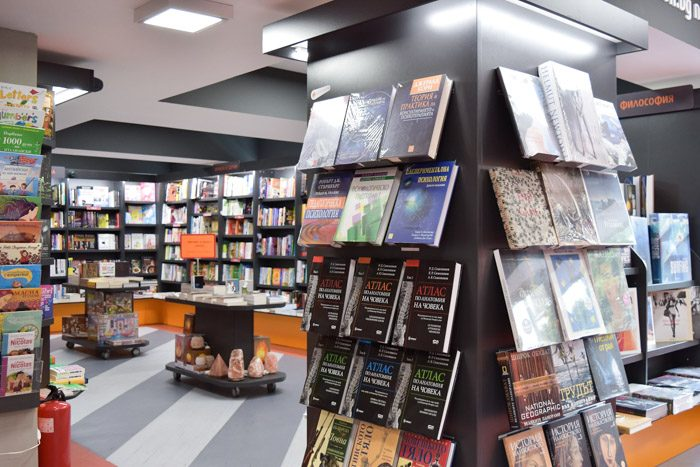 Interior of Helicon Books, bookstore in Sofia, Bulgaria. Black bookshelves and small tables are filled with neatly stacked books.