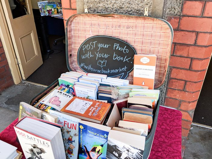 Melbourne Book Market at the Abbotsford Convent, an assortment of bocks stacked inside a vintage suitcase. A blackboard shaped like a speech bubble reads 'Post your photo with your book! #melbournebookmarket'