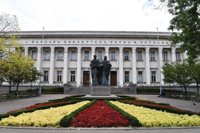 Front of the St. Cyril and Methodius National Library in Sofia, Bulgaria. An Impressive white two storey building with columns all the way along the facade. A bronze statue of two robes figures stands in front of the building, in the middle of a flowerbed of red, yellow and green geometric design.