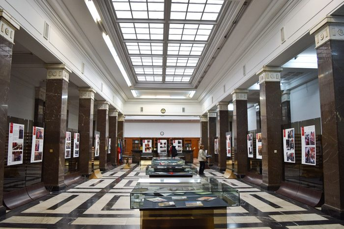 Interior of the St. Cyril and Methodius National Library in Sofia, Bulgaria. A large skylight runs the length of the ceiling. Marble columns stand on each side, and glass display cases are along the center of the room. The floor tiles are a black and white geometric design.