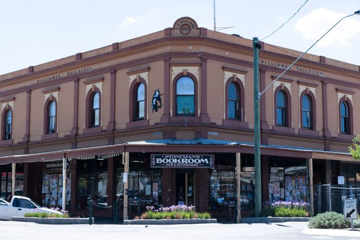 Exterior of Stoneman's Book Room in Castlemaine Victoria, a large old building painted brown with burgundy trim. Under a covered veranda a window display of books is visible.