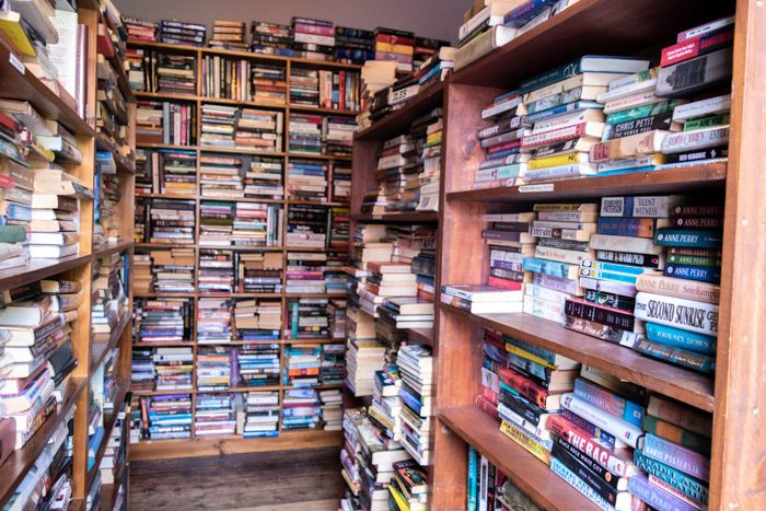 Interior of Aesop's Attic Bookshop, Woodend. Floor to ceiling bookshelves appear on all sides, books are stacked very neatly, mostly horizontally.