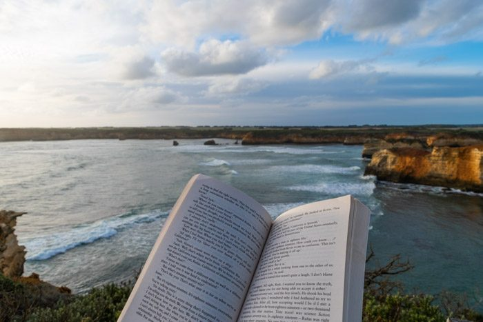 Reading a book at sunset with a view of the bay the Great Ocean Road in Victoria, Australia