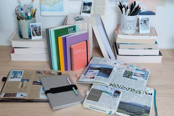 Picture of my desk at an angle with various filled out travel journal notebooks