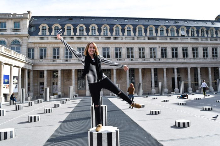 Tamsien standing on a black and white pole outside Palais Royale in Paris