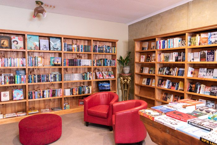 Interior of Dr B's Bookstore, Trentham. Wooden bookshelves are along two walls, and the edge of a table covered in books is just visible on the right. The shelves are sparsely  stacked with books, many books are facing forward, and two shelves are empty. There are two red tub chairs and a round red footstool in the centre of the room. Oddly, there is a sculpture of a chicken and 4 eggs on the ceiling.