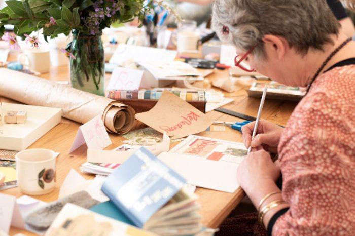 Creative Journaling Workshop, Melbourne. A seated woman works on an open notebook, surrounded by journals, paper scraps and a vase of flowers.