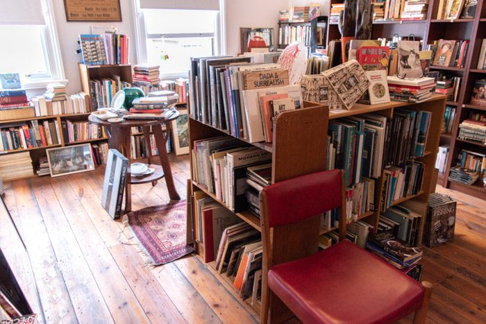 Interior of Long Story Short Secondhand Books and Music. Another view of the cosy room, low bookshelves sit underneath two windows, the smaller wooden bookshelves are in the foreground with a red leather covered chair, and the large dark wooden bookshelves can be seen in the background.