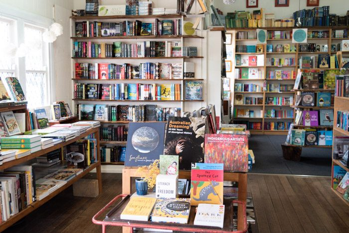 Interior of New Leaves. A bright, open bookstore with neat shelves on all walls and windows on the left. A display in the foreground on a table features books by Aboriginal authors.