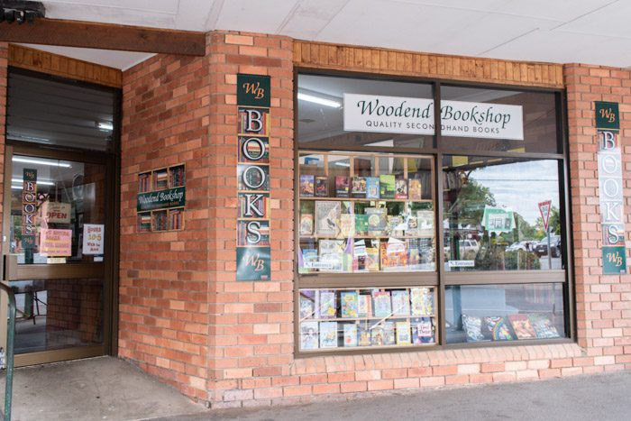 Exterior of the Woodend Bookshop, Woodend. A simple orange brick facade has a large window through which a display of books can be seen.  Multiple signs say 'WB Books' and a white sign in the window reads 'Woodend Bookshop, Quality secondhand books'.