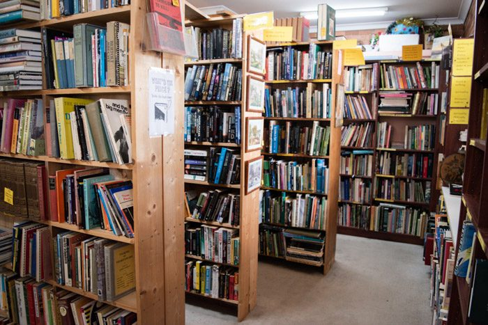 Interior of the Woodend Bookshop. Four rows of bookshelves can be seen, all stacked with books. There are bright yellow signs at the top of each shelf indicate the genres or topic of the books.