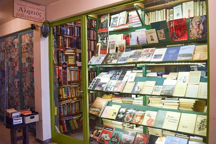 Front of Alfios Bookstore, Athens, Greece. A large window occupies most of the space, along with a glass door. Both have a bright green painted frame. books fill every space visible through the window and the door.