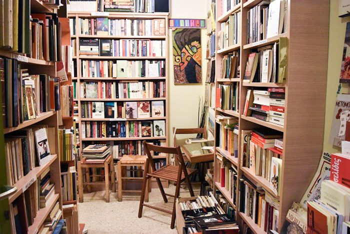 Inside Alfios Bookstore, Athens, Greece.  Colourful books are neatly stacked on wooden bookshelves. Two stools and a couple of chairs complete the scene, and an abstract artwork in brown and green hangs on the wall.