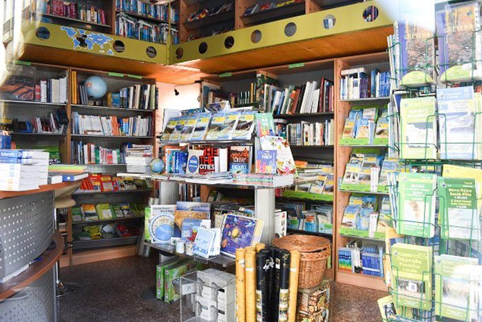 Inside Anavasi, Athens, Greece. A small crowded shop is visible, maps and guide books are visible on every surface.