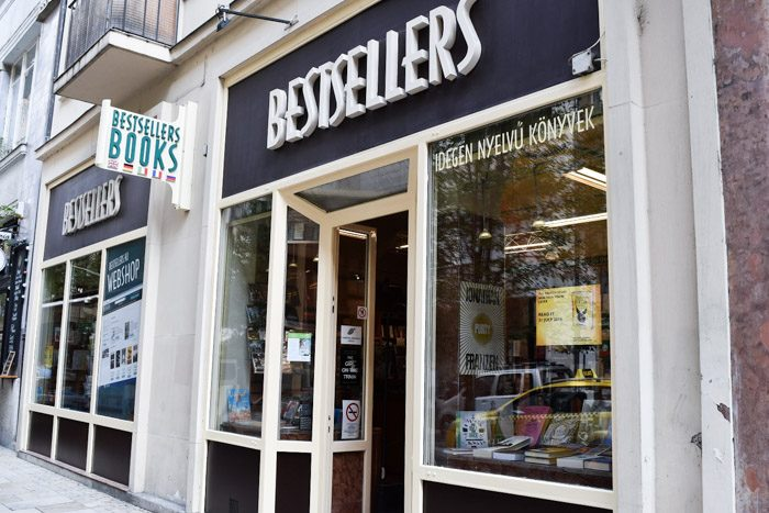 Angled photo of the front of Bestsellers displaying a white trim shopfront and windows that display the inside of the bookshop.