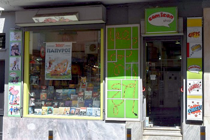 Front of Comicon, Athens, Greece. Vivid lime green signs decorate the shop front. The window display has various comic books.