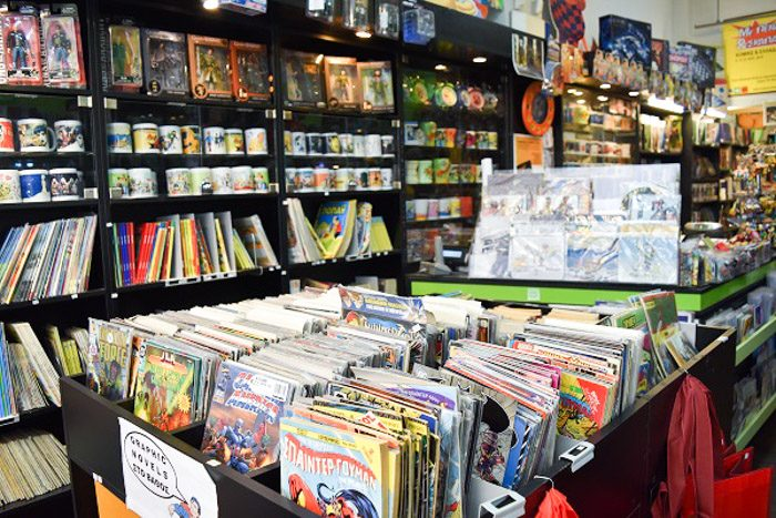 Inside Comicon, Athens, Greece. Comic books are neatly stacked in the forground and on bookshelves. Various figurines and mugs with comic book character designs can be seen on the shelves too.