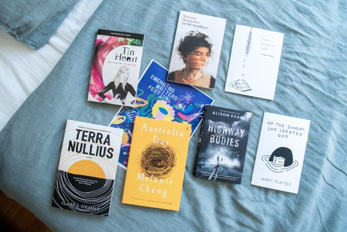 Books from Emerging Writer's Festival 2019, lying face up on a bed with pale blue sheets. The titles are: Tin Heart, From Grains to Gold, All My Goodbyes, On The Sunday She Created God, Highway Bodies, Australia Day, Terra Nullius.