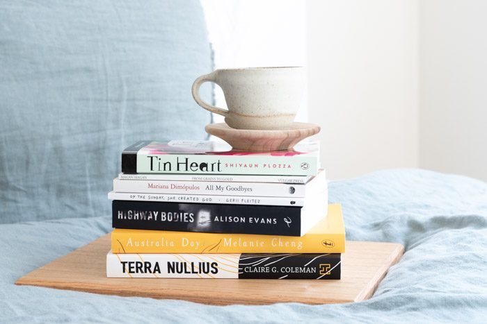 Stack of books from Emerging Writer's Festival 2019, on a bed with pale blue sheets. The titles from top to bottom are: Tin Heart, From Grains to Gold, All My Goodbyes, On The Sunday She Created God, Highway Bodies, Australia Day, Terra Nullius.