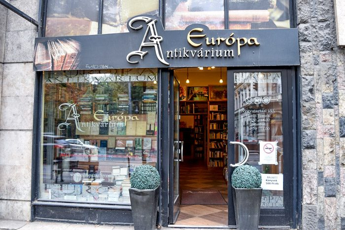 Picture of the front of Europa Antikvarium, which is a black facade and ornate sign lettering above the entrance.
