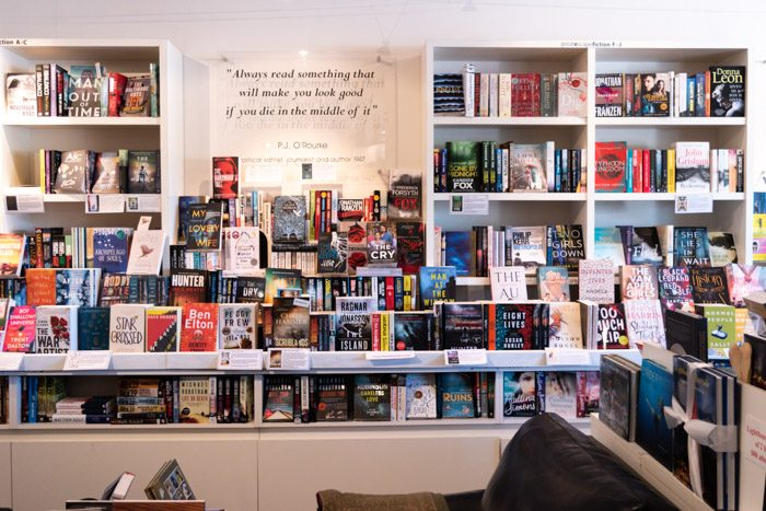 "Picture of the inside of Great Escape Books, showing a huge range of books on white shelves. There's also a sign with a quote on it that reads ""Always read something that will make you look good if you die in the middle of it"" by PJ O'Rourke."