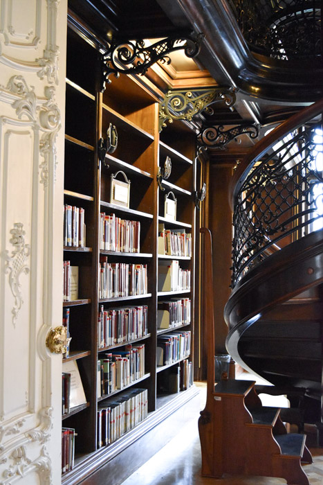 The interior of the Metropolitan library, displaying part of the spiral staircase and a range of antique books on sturdy wooden bookshelves.