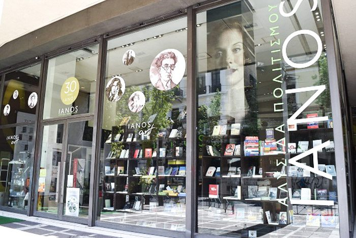 Front of Ianos Art, Athens, Greece. The largest shopfront of all the shops in this post, huge glass windows and double glass doors are decorated with circular decals of famous authors. Oscar Wilde is the most easily recognisable. Inside large black bookshelves filled with books can be seen.