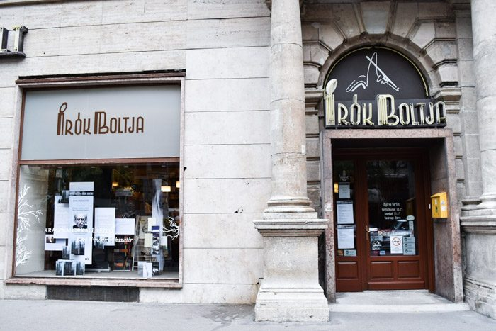 The front of this bookshop, with a heavy stone facade and art deco lettering above an inset wooden door.