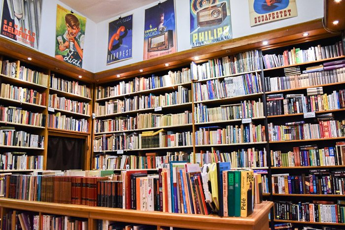 Inside Kozponti Antikvarium, with large well-lit bookshelves and vintage posters above them.