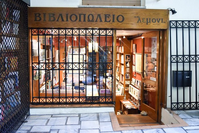 Front of Lemoni, Athens, Greece. A small shop front with a wooden sign above the window and door. The window is barred with black iron bars. Steps are visible leading down into the shop which looks warm and cosy.