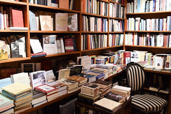 Wooden bookshelves are filled with books, and a small black and white striped chair is visible in the right corner.