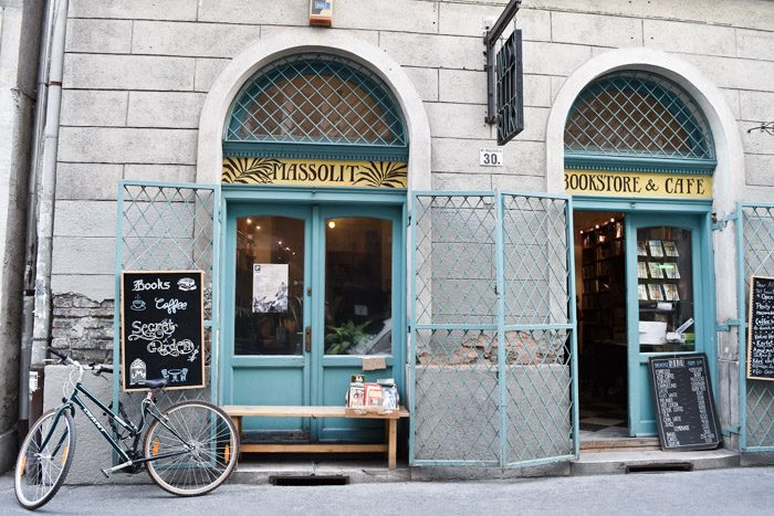 Two sets of blue arched double doors with handpainted signs above them that say 'Massolit Bookstore & Cafe', alongside several chalkboards and one bicycle.
