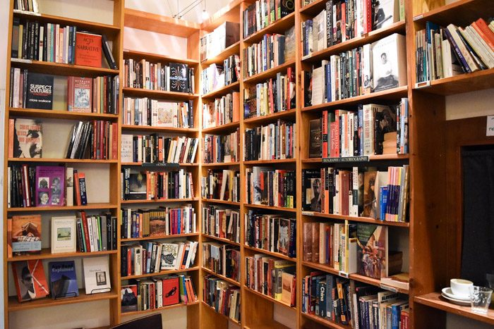A corner space with wooden bookshelves and a range of secondhand books.