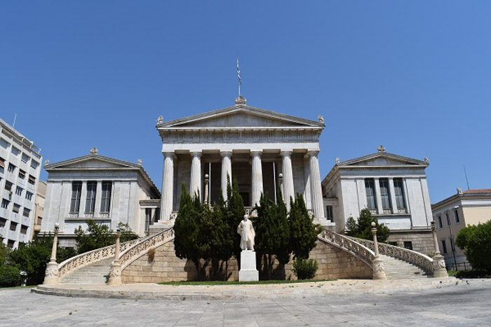 Front of the National Library of Greece, and imposing building with six columns supporting a peaked roof and a curved staircase leading to the front.