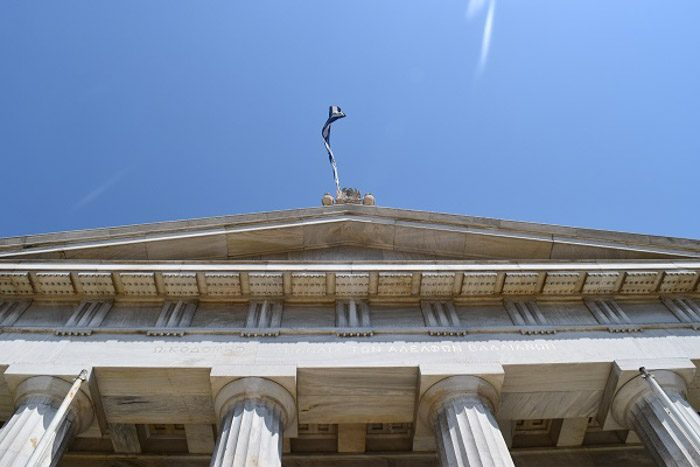 Front of the National Library of Greece, as seen from the staircase looking up. A Greek flag is waving against a blue sky.