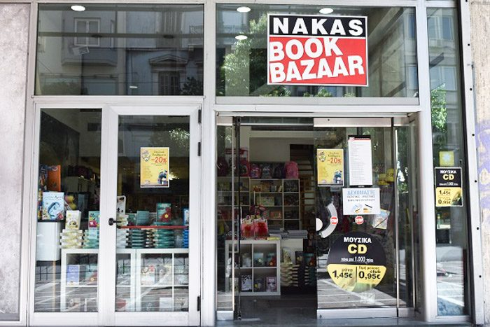 Exterior of Nakas Book Bazaar, Athens, Greece. A modern glass-fronted building. The only defining feature is a large black, white and red sign that reads 'Nakas Book Bazaar'.