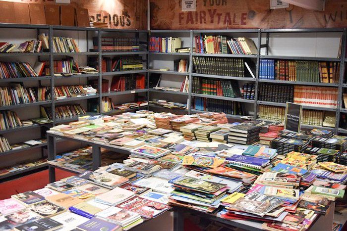 Inside Nakas Book Bazaar, Athens, Greece. Industrial style metal bookshelves line the walls and have an assortment of books on them. Some shelves are empty. The centre of the room is occupied by a table covered in books.