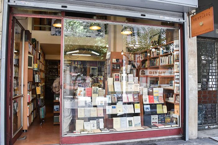 Front of Nautilus Bookstore, Athens, Greece. A large square window reveals a display of books. An open doorway to the left shows wooden bookcases.